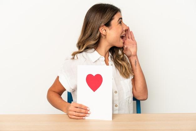 Joven mujer caucásica sosteniendo una tarjeta de san valentín aislada gritando y sosteniendo la palma cerca de la boca abierta.