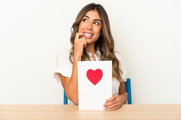Joven mujer caucásica sosteniendo una tarjeta de san valentín aislada pensando relajado en algo mirando un espacio de copia.