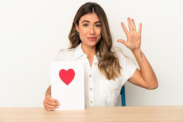 Joven mujer caucásica sosteniendo una tarjeta de san valentín aislada sonriendo alegre mostrando el número cinco con los dedos.