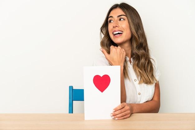 Joven mujer caucásica sosteniendo una tarjeta de san valentín puntos aislados con el dedo pulgar, riendo y sin preocupaciones.