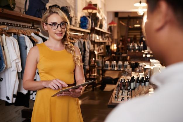 Joven mujer caucásica con tableta hablando con hombre irreconocible en boutique