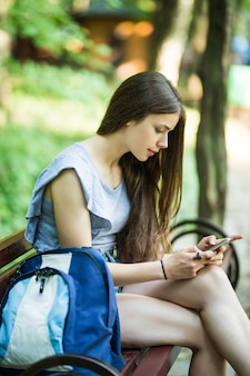 Joven mujer caucásica con un teléfono celular, sentada en un parque en un banco de madera, leyendo un sms.