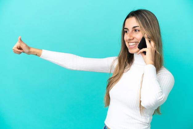 Joven mujer caucásica mediante teléfono móvil aislado sobre fondo azul dando un pulgar hacia arriba gesto