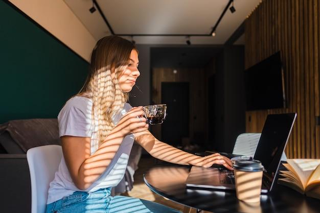 Joven mujer caucásica tomando café en la cocina, trabajando con el portátil en la mañana soleada