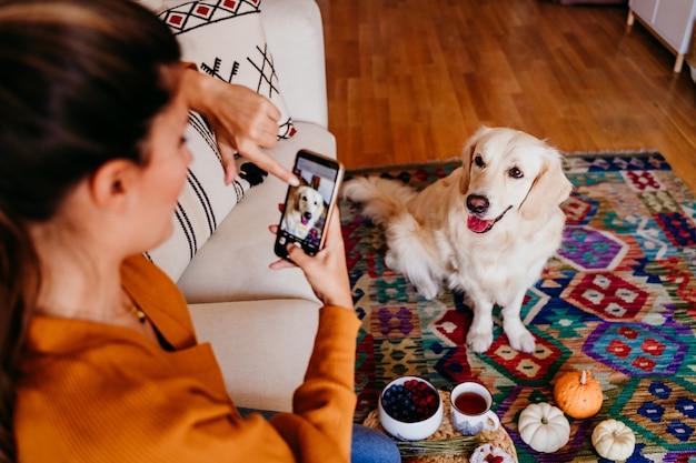 Joven mujer caucásica tomando una foto de su perro golden retriever con teléfono móvil