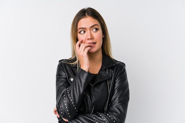 Joven mujer caucásica vistiendo una chaqueta de cuero negro mordiéndose las uñas, nerviosa y muy ansiosa.