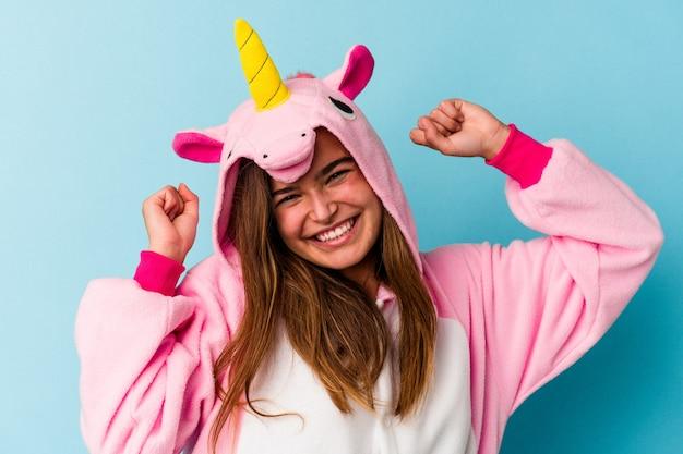 Joven mujer caucásica vistiendo un pijama de unicornio divirtiéndose aislado sobre fondo azul.