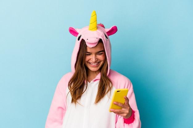 Joven mujer caucásica vistiendo un pijama de unicornio sosteniendo un teléfono móvil aislado sobre fondo azul.
