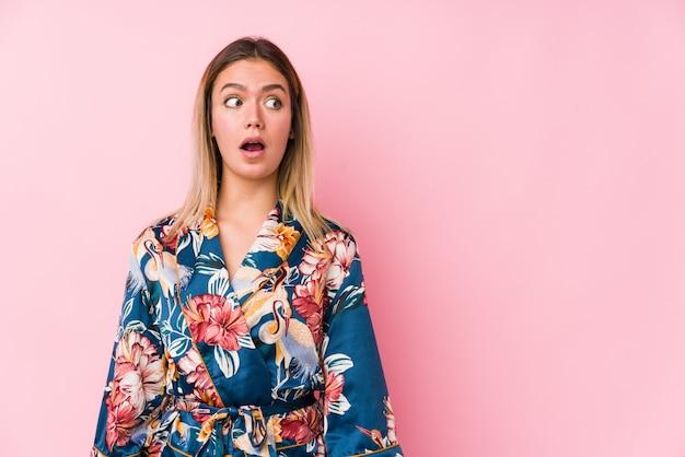 Joven mujer caucásica vistiendo pijamas se sorprendió por algo que ella ha visto.