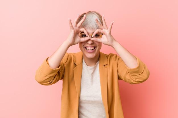 Joven mujer caucásica vistiendo una ropa casual de negocios que muestra bien firmar sobre los ojos