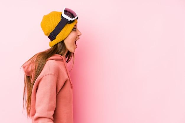 Joven mujer caucásica vistiendo una ropa de esquí aislado gritando hacia un espacio de copia