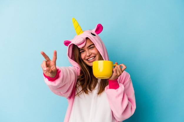 Joven mujer caucásica vistiendo un traje de unicornio sosteniendo una taza aislada