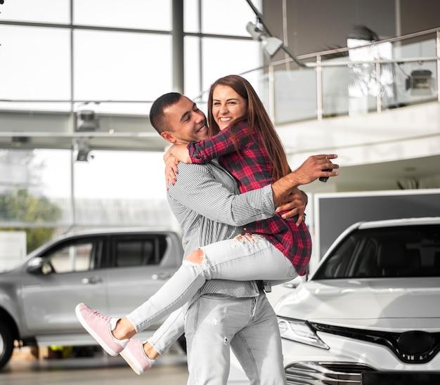 Joven y mujer celebran auto nuevo