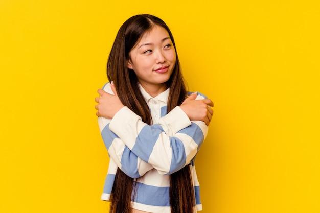 Joven mujer china abraza, sonriendo despreocupada y feliz.