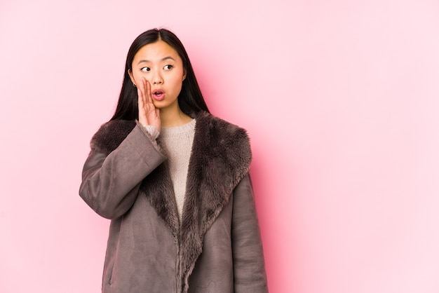 Joven mujer china con un abrigo aislado está diciendo una noticia secreta de frenado en caliente y mirando a un lado