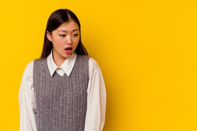 Joven mujer china aislada sobre fondo amarillo conmocionada por algo que ha visto.