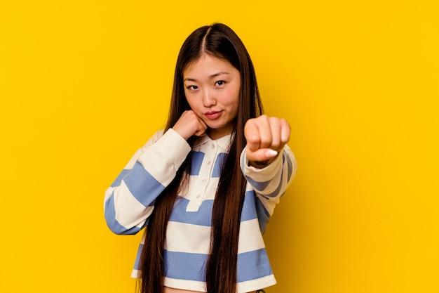 Joven mujer china aislada sobre fondo amarillo lanzando un puñetazo, ira, luchando debido a una discusión, boxeo.