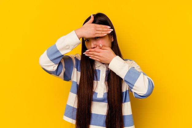 Joven mujer china aislada sobre fondo amarillo parpadea a la cámara a través de los dedos, avergonzado cubriendo la cara.