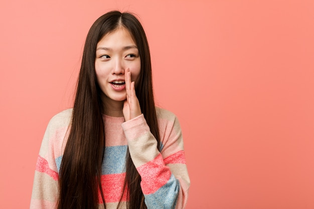 Joven mujer china fresca está diciendo una noticia secreta de frenado en caliente y mirando a un lado