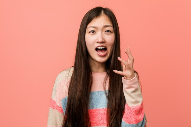 Joven mujer china fresca gritando de rabia.