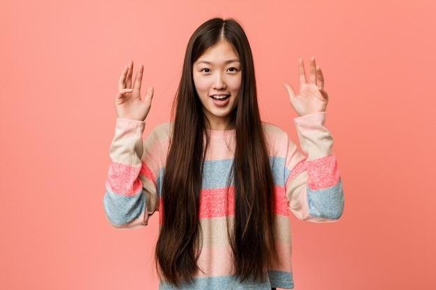 Joven mujer china fresca recibiendo una sorpresa agradable, emocionado y levantando las manos.