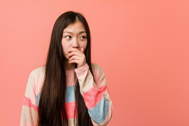 Joven mujer china fresca reflexiva cubriendo la boca con la mano