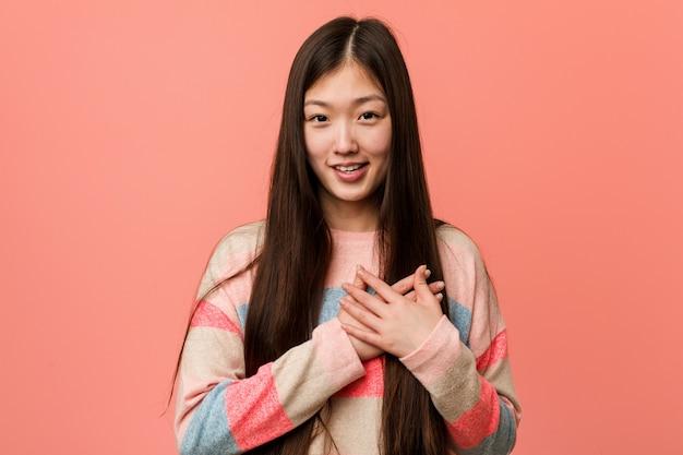 Joven mujer china fresca tiene una expresión amigable, presionando la palma contra el pecho. concepto de amor