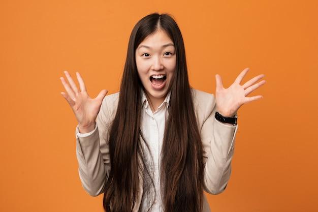 Joven mujer china de negocios celebrando una victoria o éxito