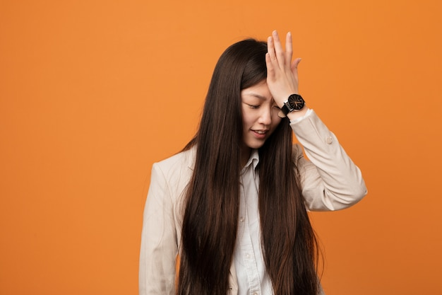 Joven mujer china de negocios olvidando algo, golpeándose la frente con la palma y cerrando los ojos.