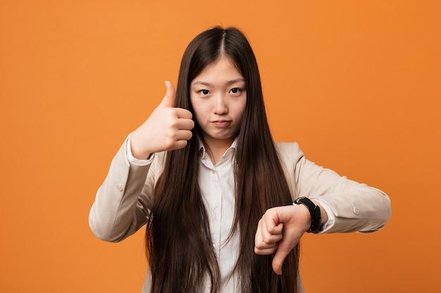Joven mujer china de negocios que muestra los pulgares hacia arriba y hacia abajo, difícil elegir el concepto