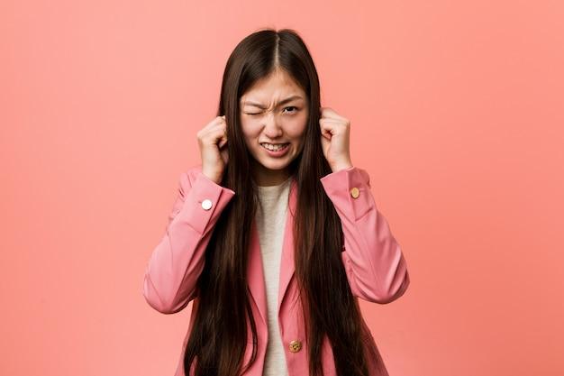 Joven mujer china de negocios vistiendo traje rosa cubriendo las orejas con las manos