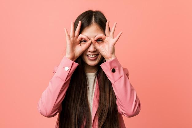 Joven mujer china de negocios vistiendo traje rosa mostrando signo bien sobre los ojos