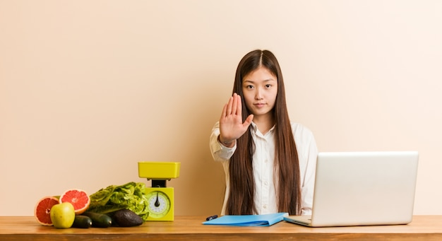 Joven mujer china nutricionista que trabaja con su portátil de pie con la mano extendida mostrando la señal de stop, impidiéndole.