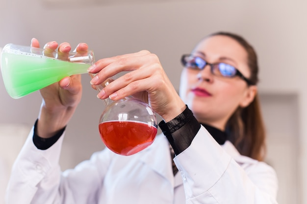 Joven mujer científica en un laboratorio mezclar reactivos