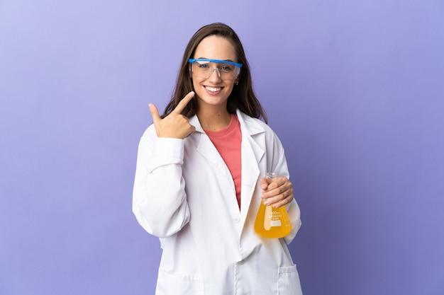 Joven mujer científica sobre pared aislada dando un pulgar hacia arriba gesto