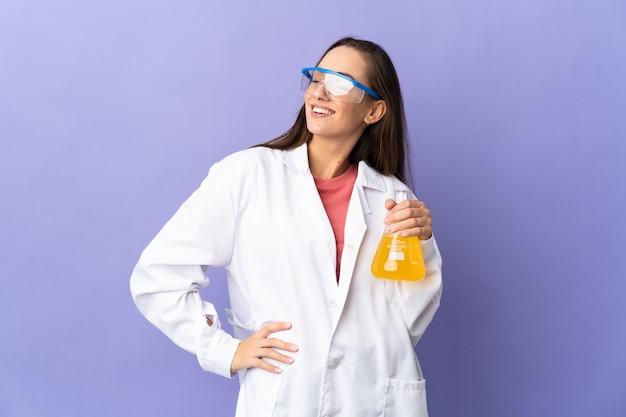 Joven mujer científica sobre pared aislada posando con los brazos en la cadera y sonriendo