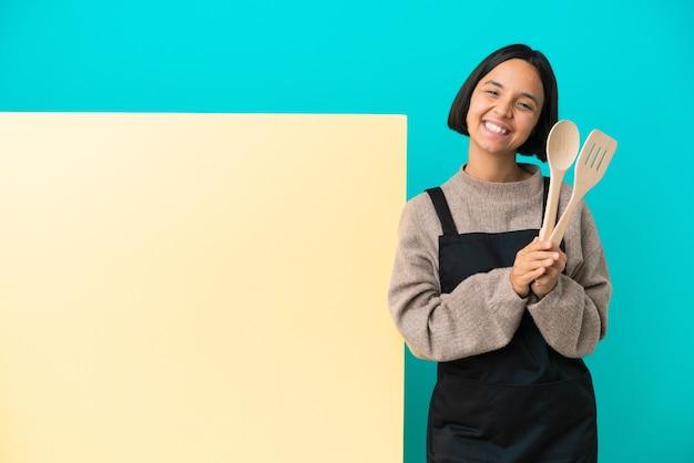 Joven mujer cocinera de raza mixta con un gran cartel aislado sobre fondo azul aplaudiendo después de la presentación en una conferencia