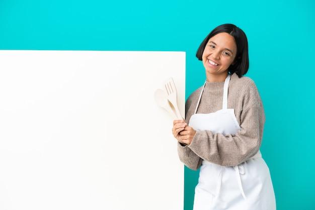 Joven mujer cocinera de raza mixta con un gran cartel aislado sobre fondo azul aplaudiendo