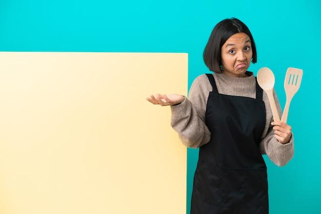 Joven mujer cocinera de raza mixta con un gran cartel aislado sobre fondo azul con dudas mientras levanta las manos