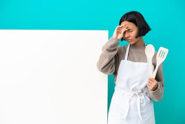 Joven mujer cocinera de raza mixta con un gran cartel aislado sobre fondo azul con expresión cansada y enferma