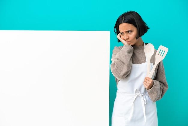 Joven mujer cocinera de raza mixta con un gran cartel aislado sobre fondo azul frustrado y cubriendo las orejas