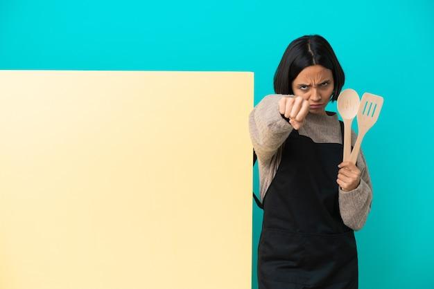 Joven mujer cocinera de raza mixta con un gran cartel aislado sobre fondo azul con gesto de lucha