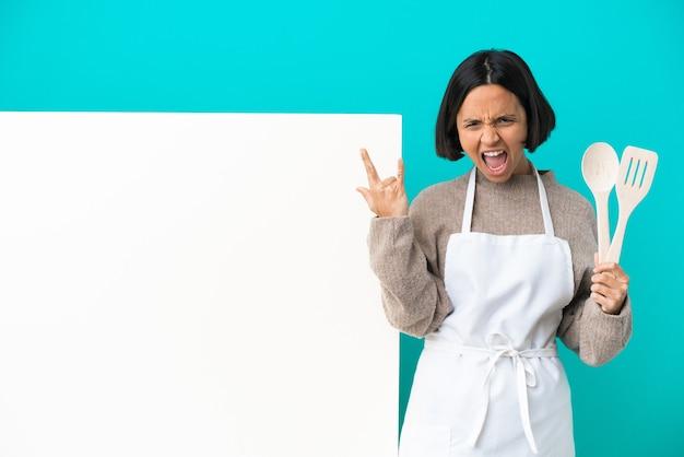 Joven mujer cocinera de raza mixta con un gran cartel aislado sobre fondo azul haciendo gesto de cuerno