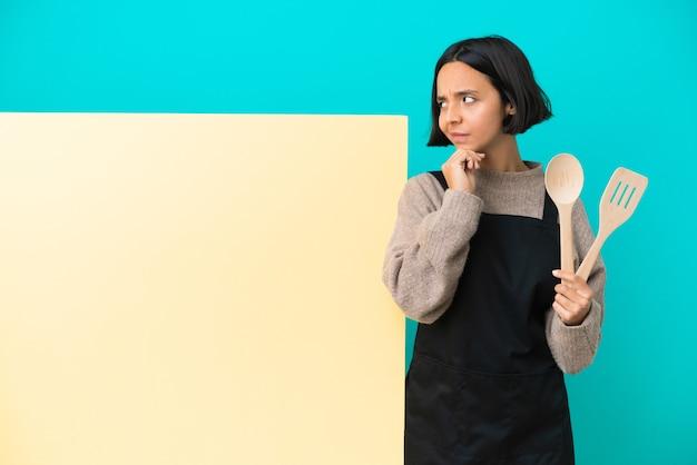 Joven mujer cocinera de raza mixta con un gran cartel aislado sobre fondo azul y mirando hacia arriba