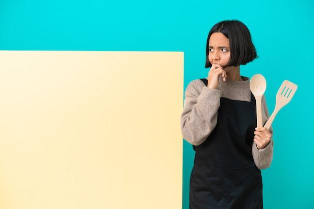 Joven mujer cocinera de raza mixta con un gran cartel aislado sobre fondo azul que tiene dudas y con expresión de la cara confusa