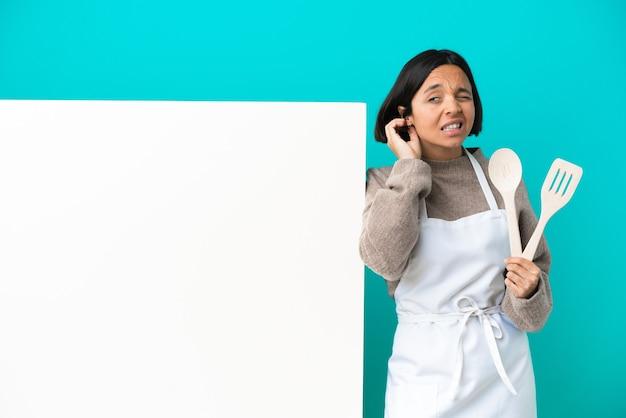 Joven mujer cocinera de raza mixta con un gran cartel aislado sobre fondo azul riendo