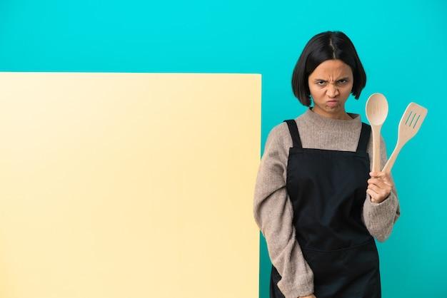 Joven mujer cocinera de raza mixta con un gran cartel aislado sobre fondo azul sintiéndose molesto