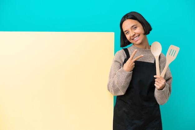 Joven mujer cocinera de raza mixta con un gran cartel aislado sobre fondo azul sonriendo y mostrando el signo de la victoria