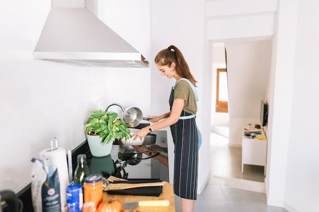 Joven mujer colar pasta hervida en el fregadero