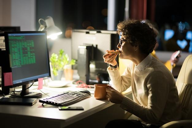 Joven mujer comiendo bocadillos en la noche